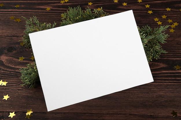 Рождественская открытка с еловыми ветками и золотыми звездами на старинных деревянных фоне.
