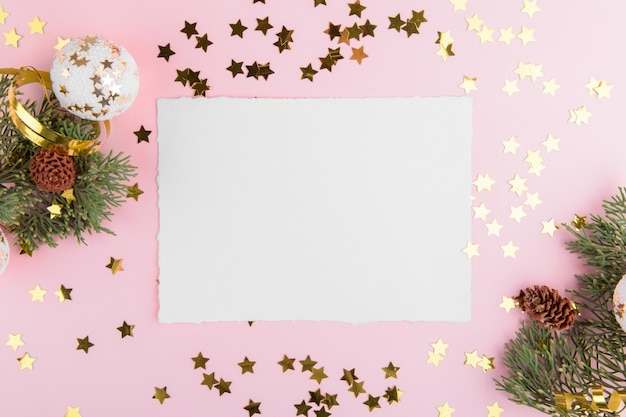 Christmas card with fir twigs and golden stars and festive decoration on a pink pastel background.