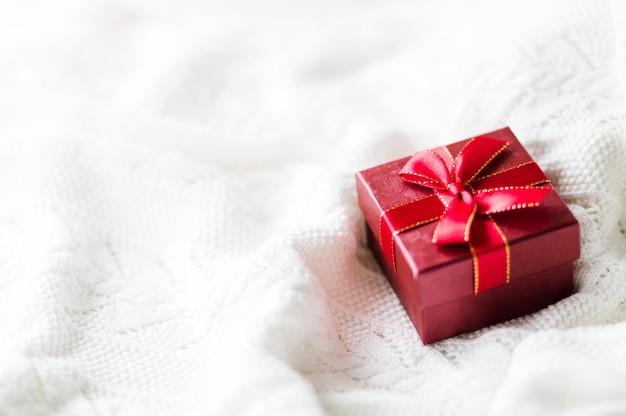 白いニットのセーターの背景にギフトボックスの赤いリボンのクリスマスカード。コピースペース。横の写真