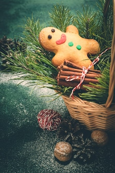 Christmas card with gingerbread man and coniferous branches in basket