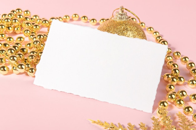 Christmas card with golden festive decoration on a pink pastel background.