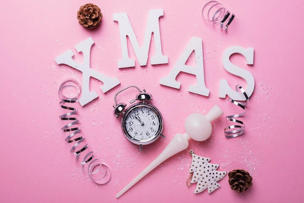 Christmas card with letters and clock on the pink background. christmas concept, top down view
