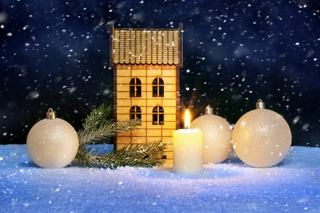 Christmas card with a lighted candle, christmas balls and a wooden toy house during a snowfall