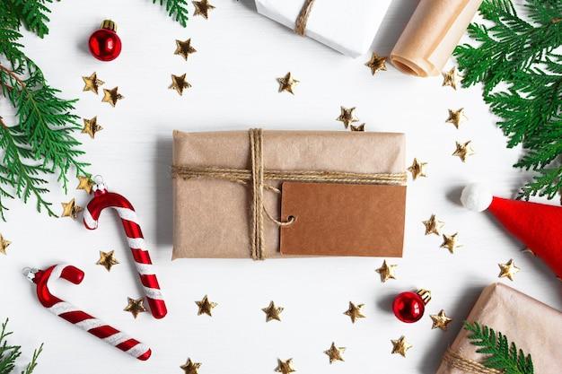 Рождественская открытка с новогодними украшениями еловые ветки подарок на белом фоне