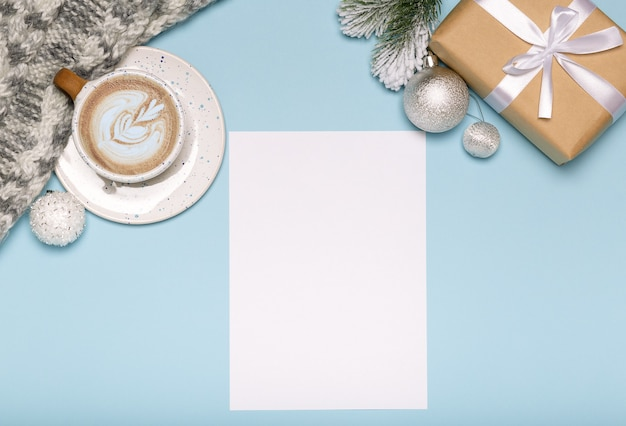 Christmas card with paper gift box and coffee on blue background