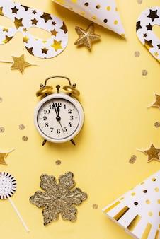 黄色の背景にパーティーハット、マスク、時計のクリスマスカード。コピースペースのあるトップダウンビュー