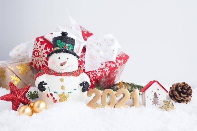 Рождественская открытка со снеговиком, подарочной коробкой и номером 2021 на снегу. копировать пространство.