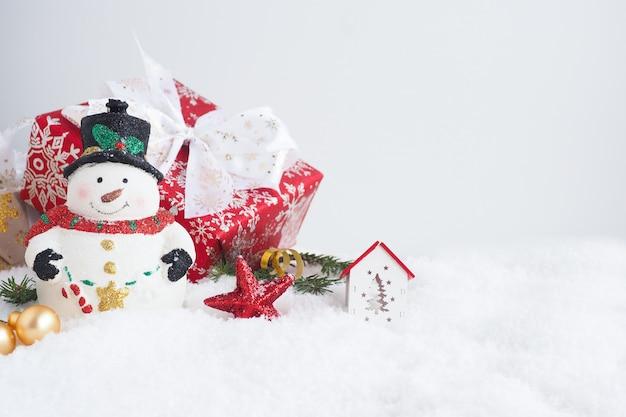 Рождественская открытка со снеговиком, подарочной коробкой, еловыми ветками, домом и звездой в снегу. копировать пространство.