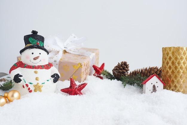 Рождественская открытка со снеговиком, подарочной коробкой, золотой свечой, еловыми ветками и шишками, домом и звездами на снегу. копировать пространство.
