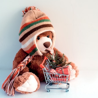 Christmas card with teddy bear and christmas gifts in supermarket trolley