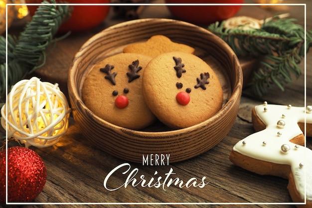 メリークリスマスの碑文が入ったクリスマスカード。木製のテーブルに鹿の顔、花輪、クリスマスツリーの枝とボールとジンジャーブレッドクッキー。