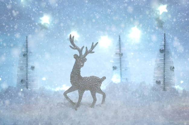 Christmas card with toy deer in a fairy forest on winter season with snow and lights.