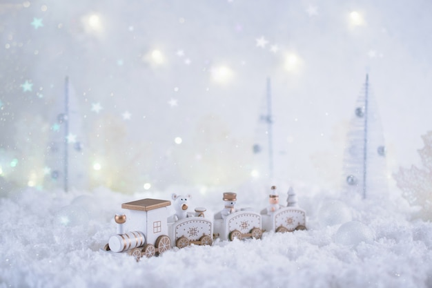 Christmas card with toy train in a fairy forest on winter season with snow and lights.