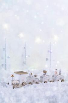Рождественская открытка с игрушечным поездом в сказочном лесу в зимний сезон со снегом и огнями.
