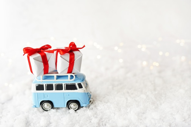 Christmas card with vintage blue bus and gift boxes in wintery landscape with snow background, new year greeting card with copy space