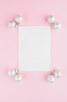 Christmas card with white balls decoration on a pink pastel background.