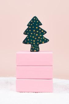 クリスマスカード。ボックスのスタック上の木製のクリスマスツリー、コピースペースのあるパステルカラーの表面。高品質の写真