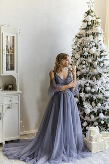 Christmas celebration. beautiful young woman in the evening dress stands in a room decorated for christmas.