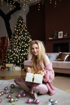Концепция празднования рождества, счастливая девушка в розовой пижаме сидит на полу с подарочной коробкой
