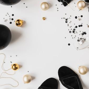 空白のコピースペースのモックアップフレームとクリスマスのお祝いのコンセプト。シャンパングラス、輝く紙吹雪、ドレス、つまらないもの、白い背景の上の靴