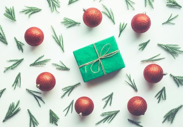 松の枝とギフトボックスと白い背景の上の赤いボール飾りの装飾とクリスマスのお祝いのコンセプト。冬の季節のアイデアのデザイン