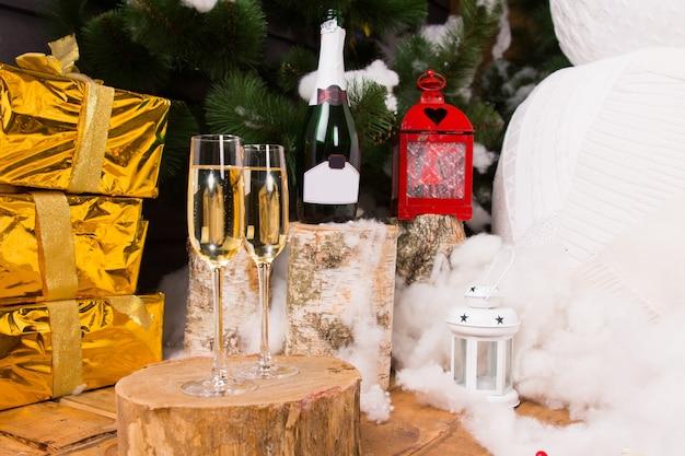 Празднование рождества с шампанским в стильных стеклянных фужерах с роскошными золотыми подарками, праздничным фонарем и снеговиком.