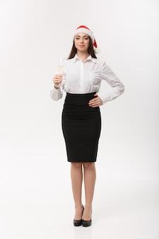 クリスマスのお祝いシャンパングラスでクリスマスを祝う若い美しいビジネス女性