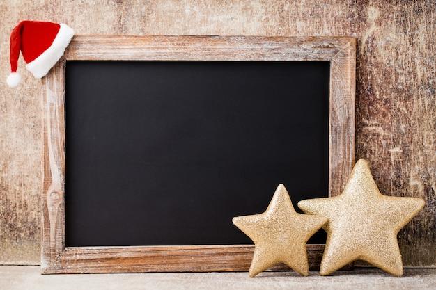 Доска рождества и украшение над деревянным фоном.