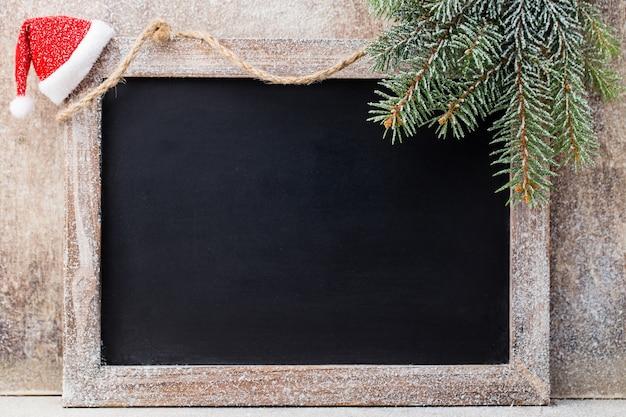 クリスマスの黒板と木製のテーブルの上の装飾。