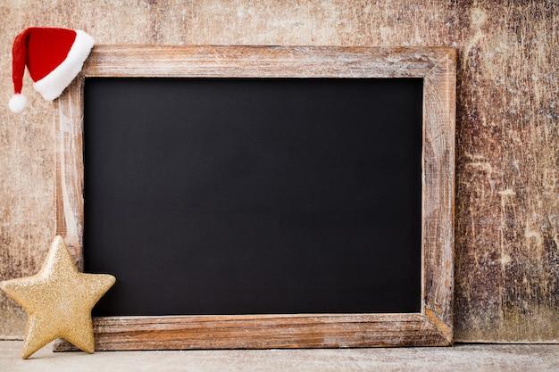 クリスマス黒板と木製のテーブルの上の装飾。