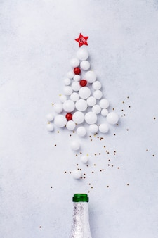 Christmas champagne bottle with sprinkles in the form of christmas tree made of red and white toys balls decorated golden confetti on white.