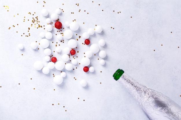 白い背景に白い色を振りかけるクリスマスシャンパンボトル。新年のコンセプト。上面図