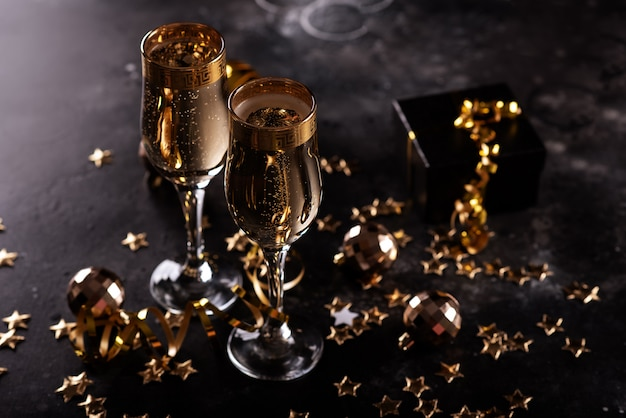 Christmas champagne, gas bubbles, confetti and blurry lights on a dark background