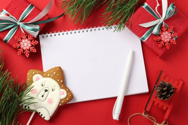 Christmas checklist or empty blank letter for santa claus with gingerbread and gifts on red.