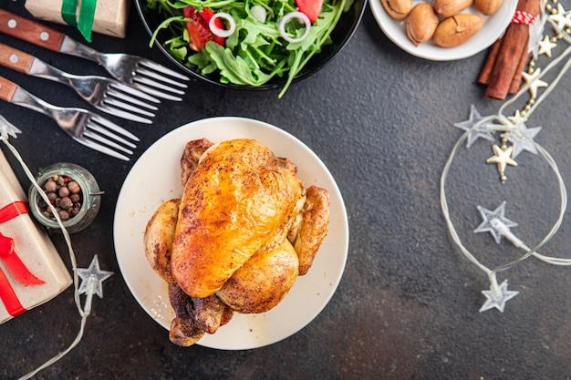 クリスマスチキンまたは七面鳥の新年のテーブルは、家族の夕食のチキンコケレットの新鮮な部分を扱います