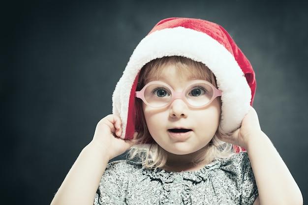 Рождественский ребенок. милая маленькая девочка в шляпе санты.