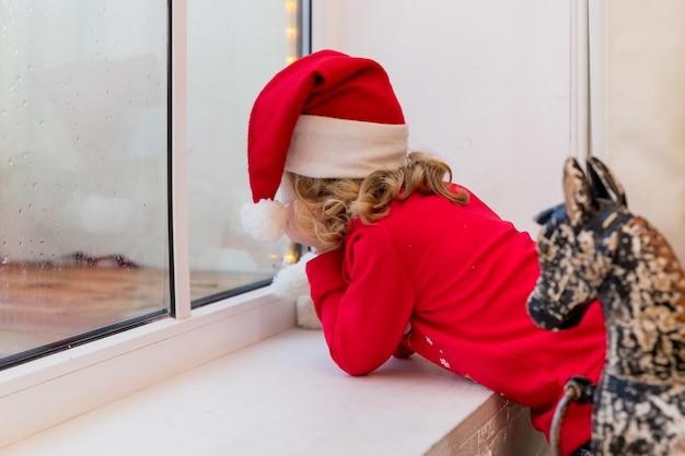 サンタ帽子のクリスマスチャイルドエルフ、エルフ。メリークリスマスとハッピーホリデー。窓際に座って冬の森を見ている少女。