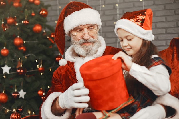 Christmas, child and gifts. santa claus brought gifts to kid. joyful little girl hugging santa.