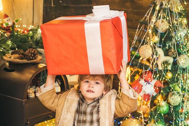 거 대 한 선물 상자를 들고 크리스마스 아이 크리스마스 트리를 장식 하는 행복 한 아이 사에서 행복 한 귀여운 아이 ...