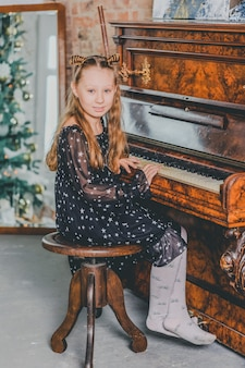 Christmas child little girl playing on piano at home. a girl plays the piano at christmas.