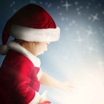 Christmas child open gift on background with sparkle and glitter