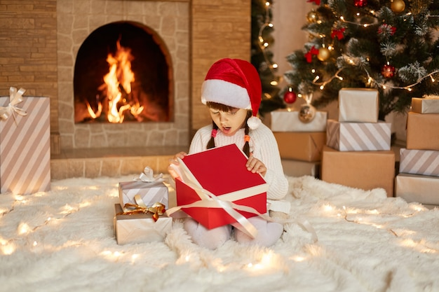 Christmas child opening present near xmas tree. Premium Photo