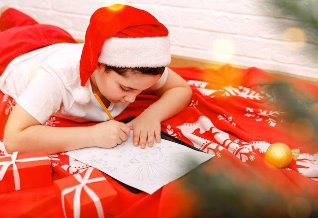 クリスマスの子供はサンタクロースに手紙を書く幸せな男の子は手紙を書く