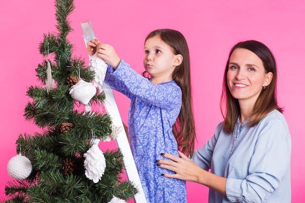 クリスマス、子供時代、人々のコンセプト-ピンクの壁に母親と一緒にクリスマスツリーを飾る踏み台に立っている子供の女の子。