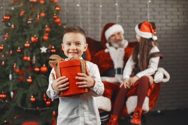 Christmas, children and gifts. santa claus brought gifts to children. joyful kids with gifts hugging santa.