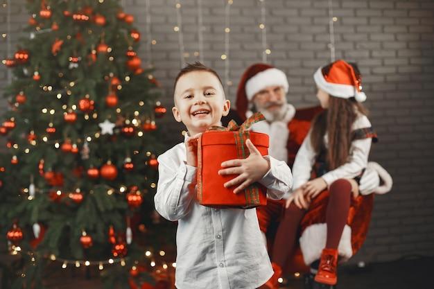 Natale, bambini e regali. babbo natale ha portato regali ai bambini. bambini allegri con doni che abbracciano babbo natale.