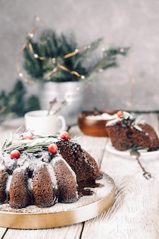 Рождественский шоколадный торт, украшенный ягодами и розмарином на столе, вертикальное фото