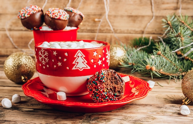 Christmas chocolate cake pops in red basket with mug of coffee with marshmallows