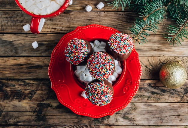 Christmas chocolate cake pops on red plate with mug of coffee with marshmallows on a rustic wooden background