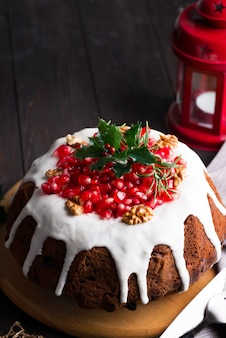 Christmas chocolate cake with white icing and pomegranate kernels on a wooden dark  with red lantern and poinsettia